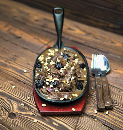 Говядина, тушенная с черносливом и кедровыми орешками
