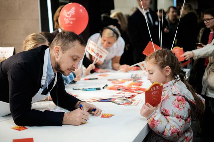 Певец Данко дает автограф юной участнице акции
